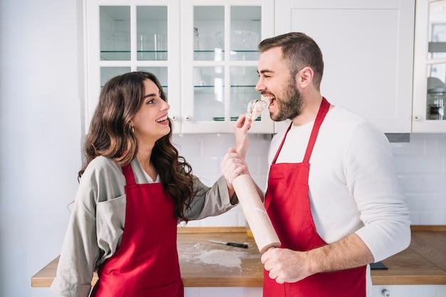 Coppie felici in grembiuli sulla cucina