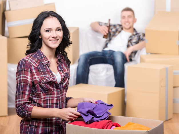 Coppie felici in nuovo appartamento con molte scatole.
