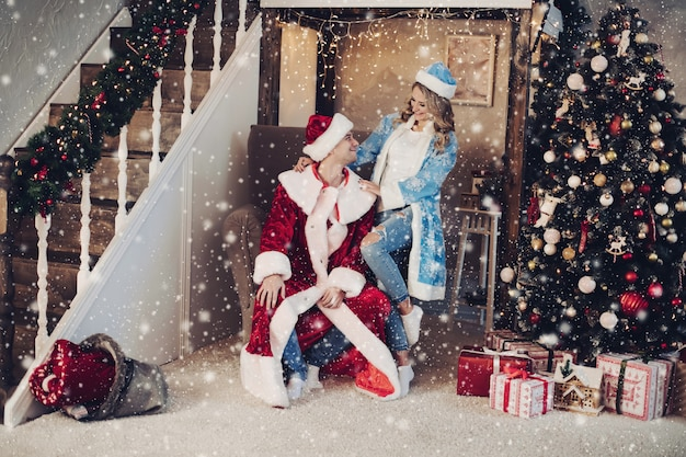 Coppie felici in ragazza della neve e costumi di babbo natale