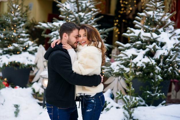 Coppie felici in vestiti caldi che si abbracciano sul dell'albero di natale con le luci. vacanze invernali, natale e capodanno.