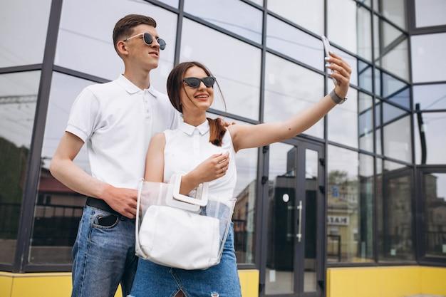Coppie felici insieme fuori nella città facendo uso del telefono
