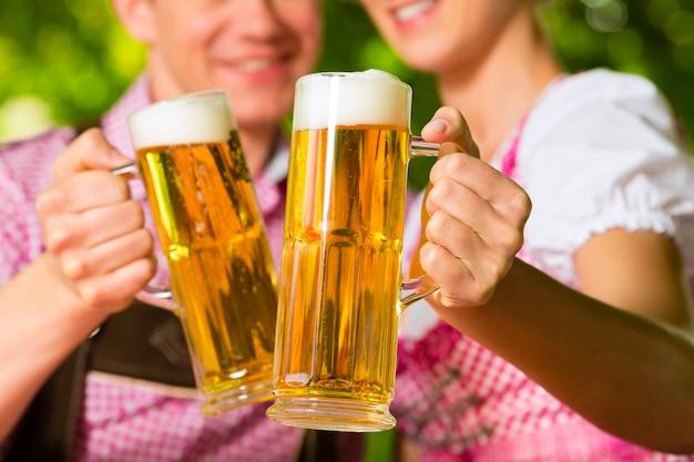 Coppie felici nel giardino della birra che beve birra
