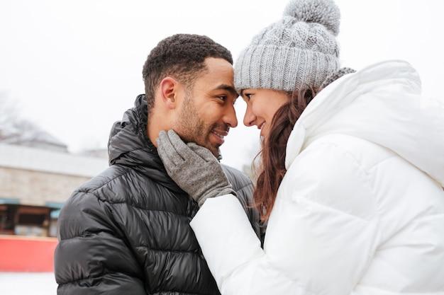 Coppie felici nell'amore che abbraccia all'aperto nell'inverno