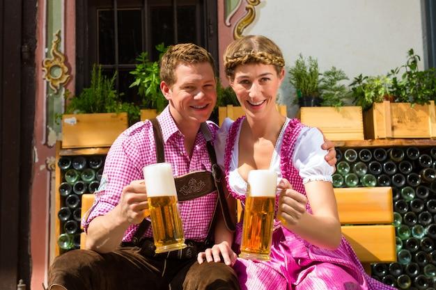Coppie felici nella birra bevente del giardino della birra