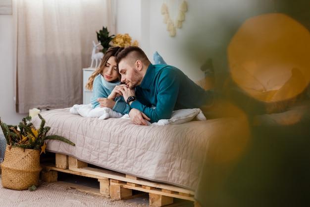 Coppie felici nella decorazione di natale a casa. capodanno, abete decorato. vacanze invernali e concetto di amore. giovani coppie felici che abbracciano e che si rilassano sullo strato comodo.