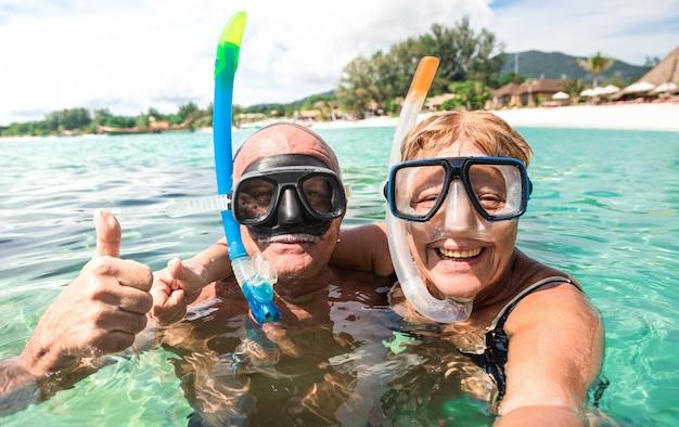 Coppie felici senior che prendono selfie alla spiaggia tropicale durante l'escursione del mare