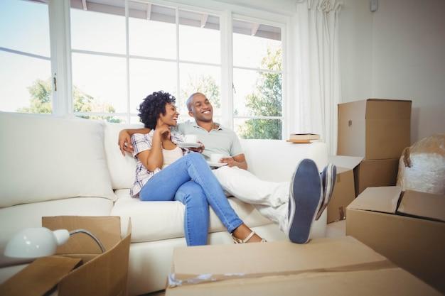 Coppie felici sul sofà che mangia caffè nella loro nuova casa