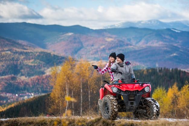 Coppie felici sulla bici del quad rosso che guida nelle montagne.