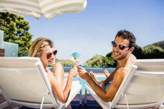 Coppie felici sullo sdraio che tiene a bordo piscina cocktail