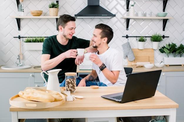 Coppie gay felici che bevono caffè e che si divertono insieme. la routine quotidiana della vita di coppia gay in cucina a casa. concetto gay, vita felice