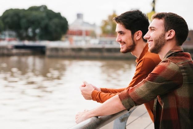 Coppie gay felici che stanno all'argine del fiume
