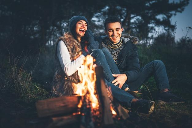 Coppie graziose che si rilassano vicino al falò nella foresta a tempo di sera