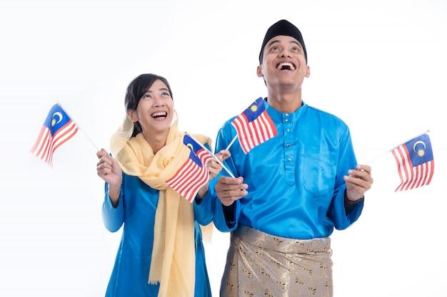 Coppie in blu che tiene la bandiera della malesia