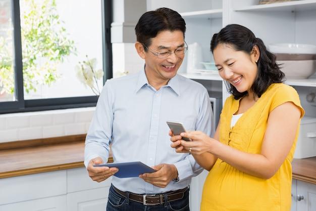 Coppie in grande aspettativa felici facendo uso della compressa e dello smartphone nella cucina