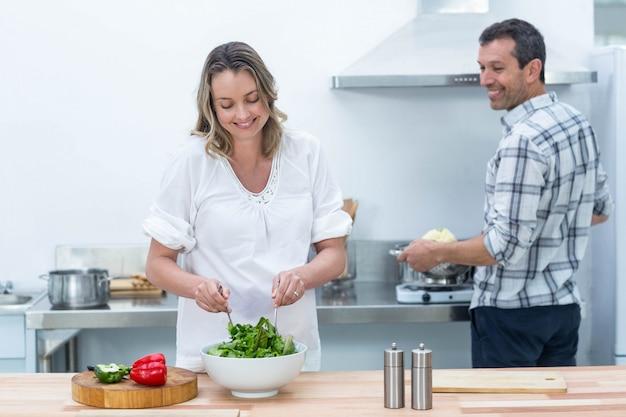 Coppie incinte che preparano insalata in cucina