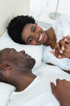 Coppie incinte che sorridono mentre rilassandosi sul letto a casa