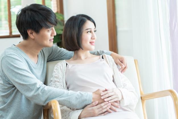 Coppie incinte emozionanti felici divertendosi a casa. la mamma e il papà in attesa allegri che si siedono sullo strato, guardano fuori dalla finestra che sorridono, ridendo. godendo il concetto di gravidanza