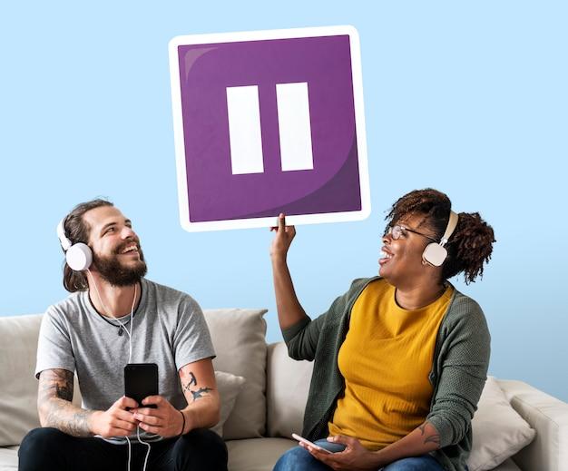 Coppie interrazziali che ascoltano la musica e che tengono un bottone di pausa