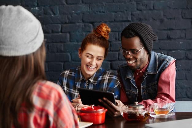 Coppie interrazziali felici che godono della connessione ad alta velocità al ristorante durante il pranzo