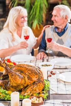 Coppie invecchiate che si siedono alla tabella con il pollo arrostito