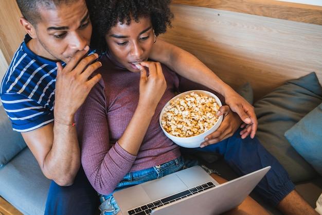 Coppie latine che guardano un film con il computer portatile a casa.
