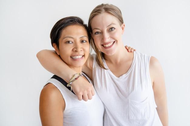 Coppie lesbiche allegre che abbracciano e che guarda l'obbiettivo