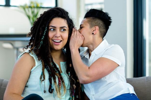 Coppie lesbiche che bisbigliano in orecchio e che sembrano sorprese