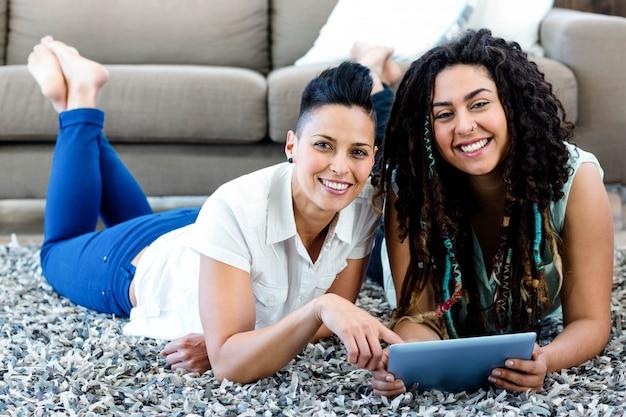 Coppie lesbiche sorridenti che si trovano sulla coperta e che utilizzano compressa digitale nel salone