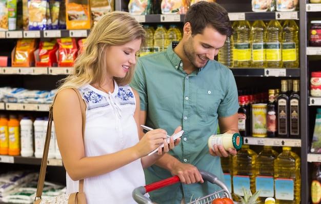 Coppie luminose sorridenti che comprano prodotti alimentari e scrittura sul taccuino