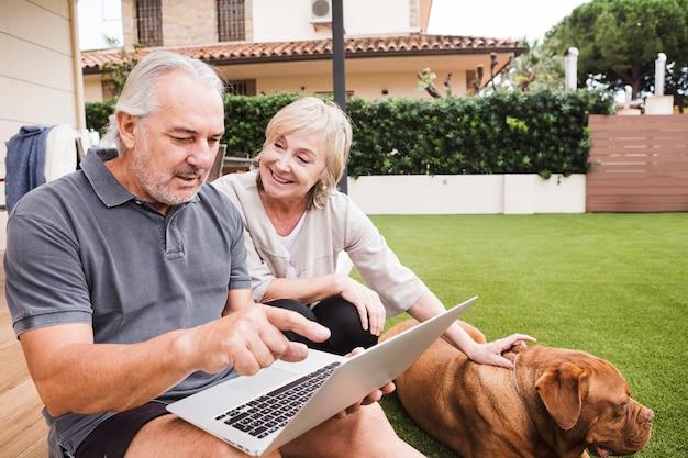 Coppie maggiori con il cane in giardino