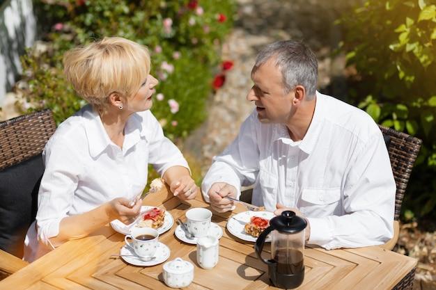 Coppie maggiori in giardino con caffè