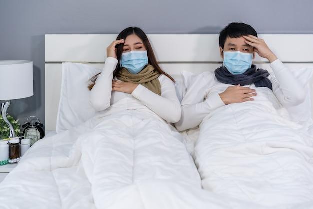 Coppie malate nell'emicrania medica della maschera e che soffrono della malattia virale e della febbre a letto, concetto di pandemia del coronavirus.