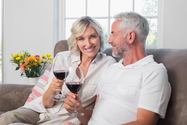 Coppie mature amorose felici con i vetri di vino in salone