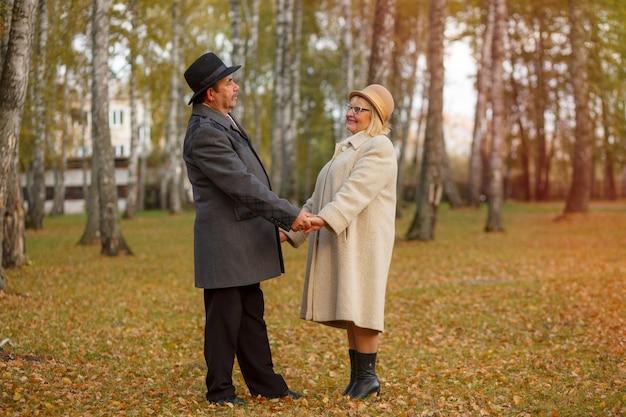 Coppie mature che camminano nel parco di autunno