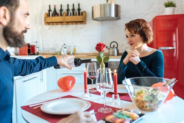 Coppie mature che hanno una cena romantica a casa per il giorno di biglietti di s. valentino e che bevono vino rosso