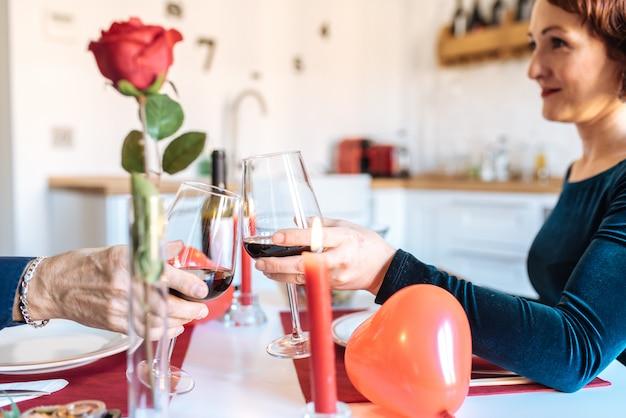 Coppie mature che hanno una cena romantica a casa per il giorno di biglietti di s. valentino e che fanno pane tostato con vino rosso