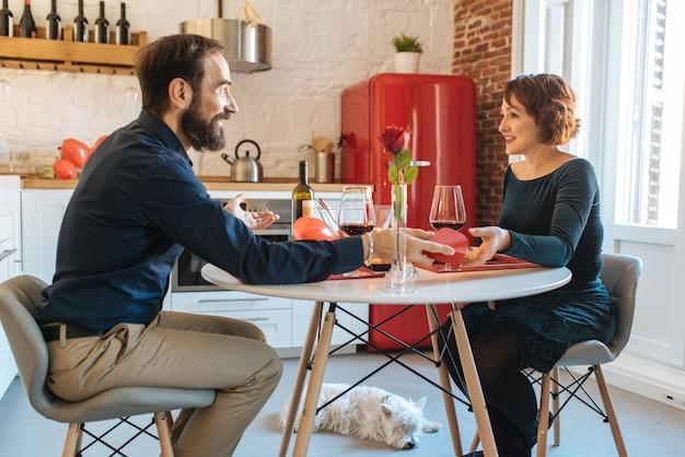 Coppie mature che hanno una cena romantica a casa per il giorno di biglietti di s. valentino
