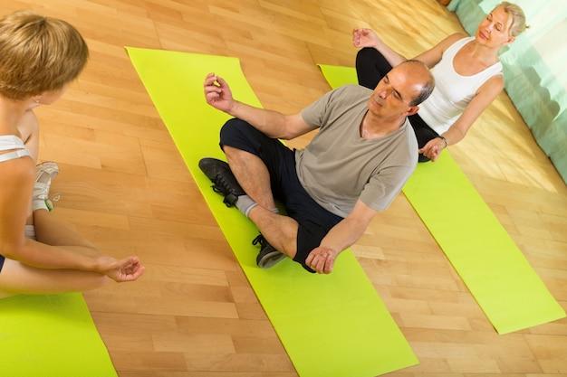Coppie mature che praticano yoga con istruttore