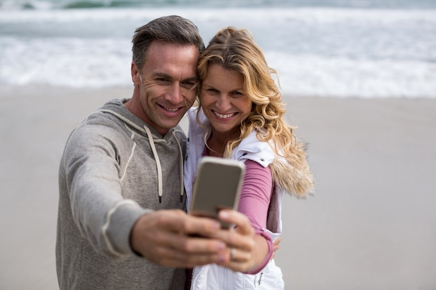 Coppie mature che prendono selfie facendo uso del telefono cellulare