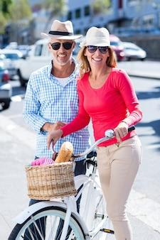Coppie mature con la bicicletta sulla via della città