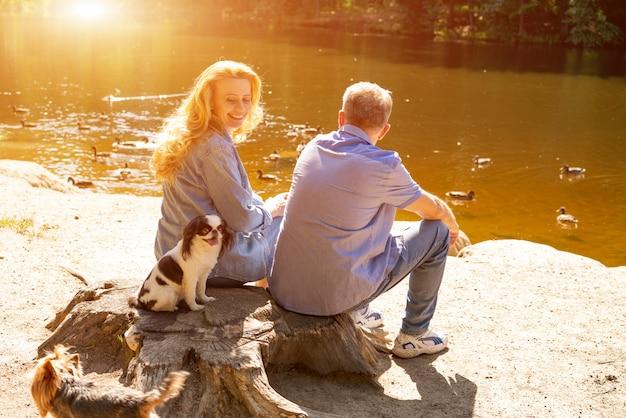 Coppie mature felici che si siedono sul lago al sole con i loro cani. concetto di vacanza in famiglia nella natura