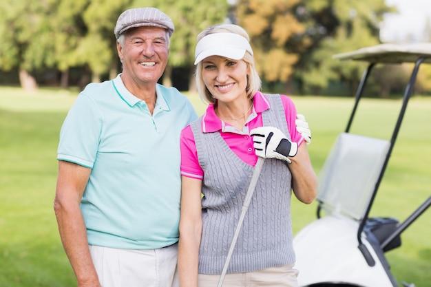 Coppie mature felici che stanno al campo da golf