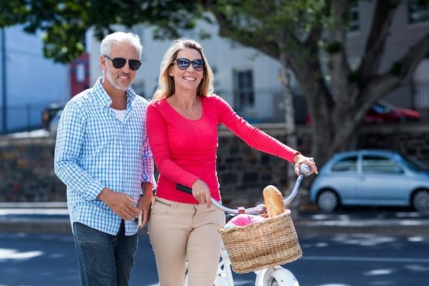 Coppie mature felici con la bicicletta in città