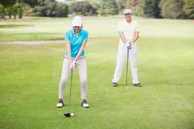 Coppie mature sorridenti che giocano golf