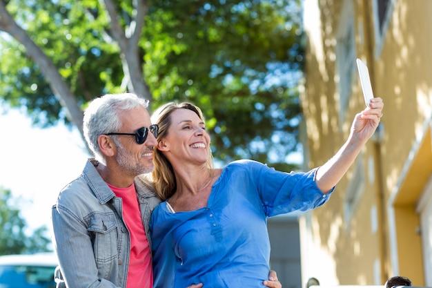 Coppie mature sorridenti che prendono selfie