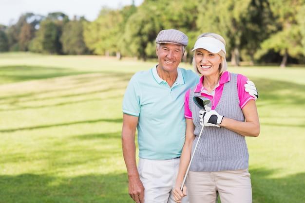 Coppie mature sorridenti che stanno al campo da golf