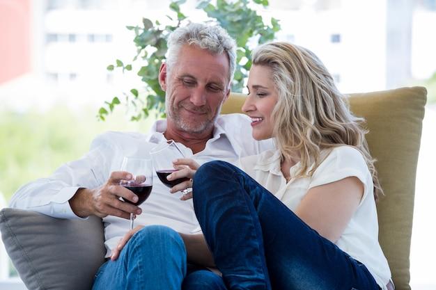 Coppie mature sorridenti che tostano vino rosso a casa