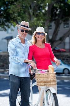 Coppie mature sorridenti con la bicicletta in città