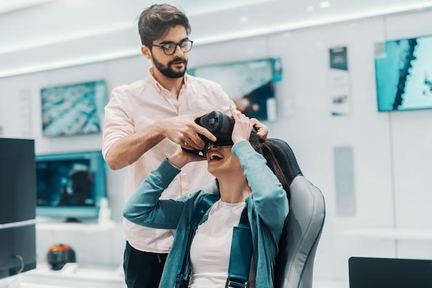 Coppie multiculturali allegre che provano la tecnologia di realtà virtuale nel deposito di tecnologia. equipaggi la donna d'aiuto per mettere gli occhiali di protezione del vr e la donna che si siedono nella sedia.