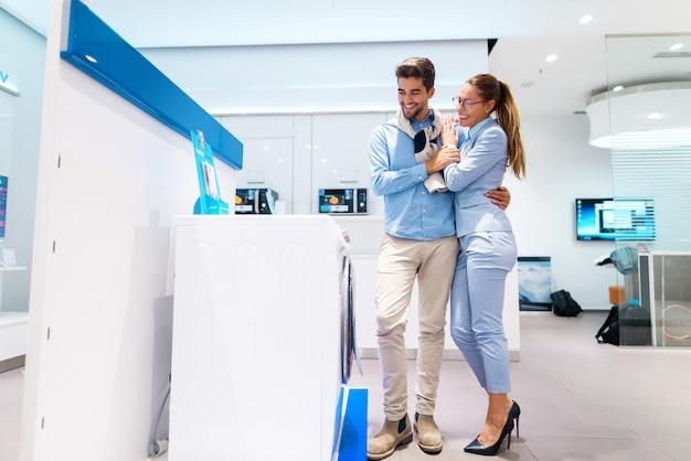 Coppie multiculturali sorridenti che cercano nuova lavatrice. uomo in piedi mentre la donna si appoggia su di lui.